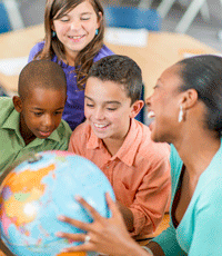 A teacher holding a world globe and three students